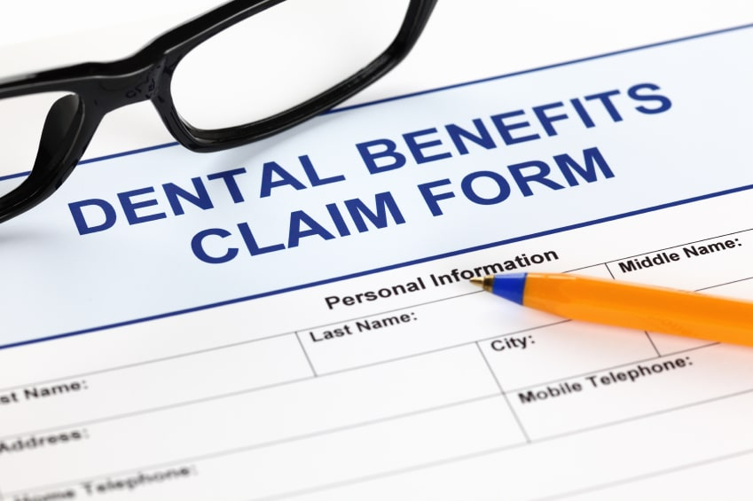 Dental benefits claim form with glasses and ballpoint pen