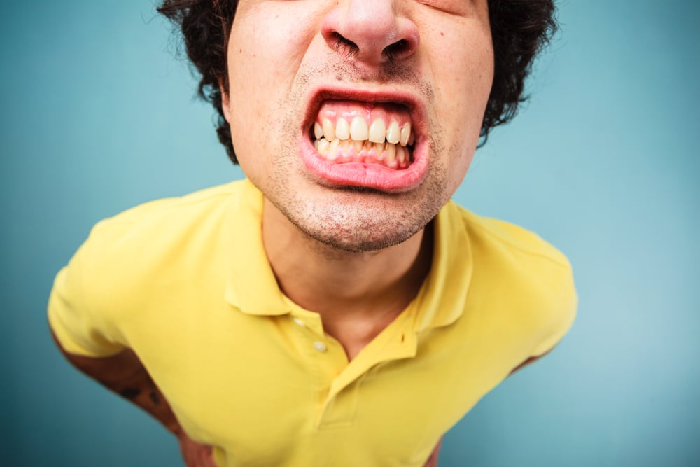 Man in a yellow shirt grinding his teeth