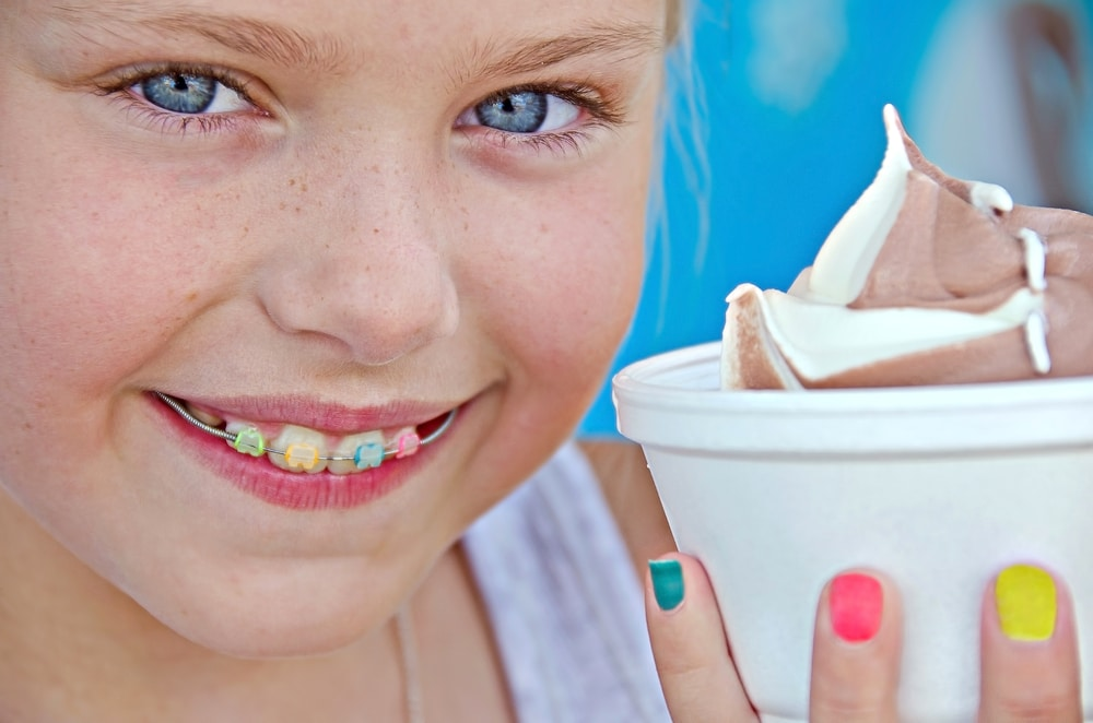 Young girl with braces eating ice cream