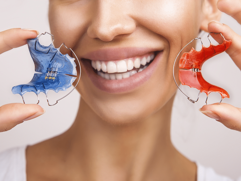 Smiling woman holding removable retainers