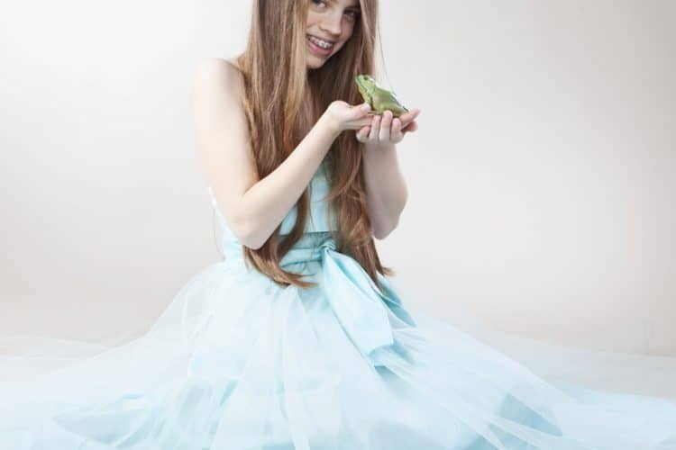 girl with braces about to kiss a frog