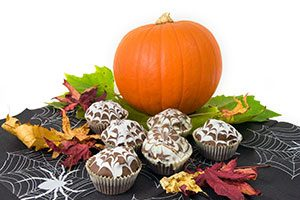 Image of six cupcakes on a table with Halloween decorations